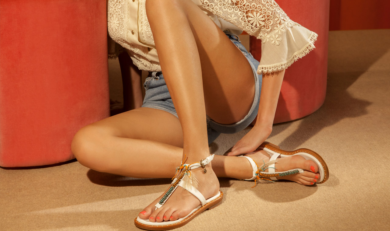Plagette infradito con bracciale alla caviglia e ricca accessoriatura dal sapore etnico. Mini studs decorativi sulla suola.